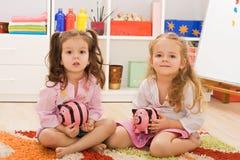 flickor som rymmer lilla piggybanks Arkivbild