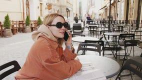 Flickor som samlar i coffee shop och talande telefon arkivfilmer