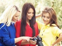 Flickor som ser foto på en kamera royaltyfria foton