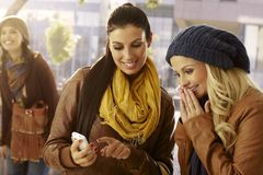 Flickor som ser foto på mobilephonen Arkivbilder