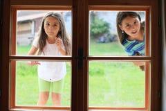 Flickor som ser in i fönster Arkivbilder
