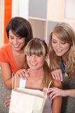 Flickor som ser i shoppingpåsar arkivbild