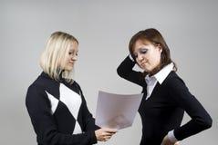 flickor som ser papper två Arkivbilder