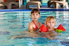 Flickor som simmar i pölen royaltyfri bild