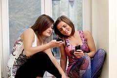 flickor som sitter fönsterbräda två Arkivfoton