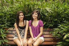Flickor som sitter i en bänk Royaltyfri Bild