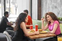 Flickor som sitter i kafét som äter snabbmat och meddelar arkivbilder