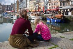 Flickor som sitter på den berömda franska staden Honfleur för bakgrund Royaltyfria Bilder