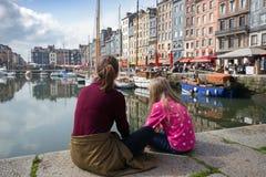 Flickor som sitter på den berömda franska staden Honfleur för bakgrund Fotografering för Bildbyråer