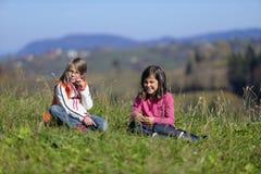 Flickor som sitter på gräs Royaltyfri Bild