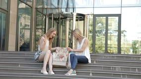 Flickor som sitter på momenten med shoppingpåsar, efter stor shopping från försäljning arkivfilmer