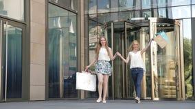 Flickor som sitter på momenten med shoppingpåsar, efter stor shopping från försäljning lager videofilmer