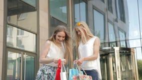 Flickor som sitter på momenten med shoppingpåsar, efter stor shopping från försäljning stock video