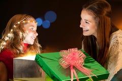 Flickor som sitter runt om julklappar Arkivfoto
