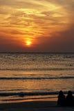 Flickor som sitter vid havet på solnedgången Fotografering för Bildbyråer