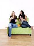 flickor som skrattar att hålla ögonen på för tv Royaltyfri Bild