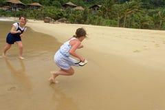 Flickor som skrattar och spelar på stranden royaltyfri fotografi