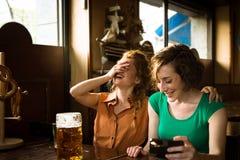 Flickor som skrattar på baren Arkivbild