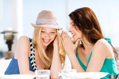 Flickor som skvallrar i kafé på stranden Arkivfoton
