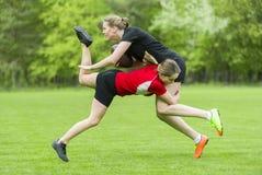 Flickor som spelar amerikansk fotboll tillsammans som ?r utv?ndig i sommar royaltyfri bild