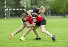 Flickor som spelar amerikansk fotboll tillsammans som ?r utv?ndig i sommar arkivfoton