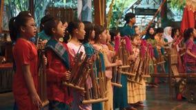 Flickor som spelar angklung under konsertshow lager videofilmer