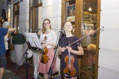 Flickor som spelar fiolen utomhus Arkivfoton