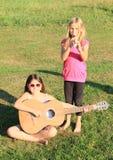 Flickor som spelar flöjten och gitarren Arkivfoto