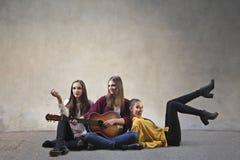 Flickor som spelar gitarren royaltyfri foto