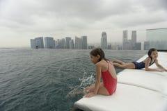 Flickor som spelar i en simbassäng Royaltyfria Bilder
