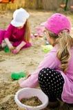 Flickor som spelar i sandlåda Royaltyfria Foton