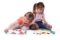 Flickor som spelar med alfabet arkivfoto