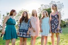 Flickor som står samman med träd i bakgrunden Royaltyfri Foto