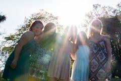 Flickor som står samman med träd i bakgrunden Arkivbilder