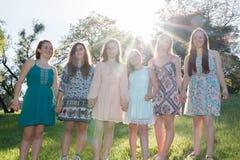 Flickor som står samman med träd i bakgrunden Royaltyfri Bild