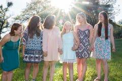 Flickor som står samman med träd i bakgrunden Arkivfoton