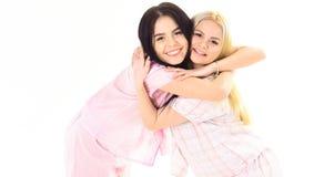 Flickor som tätt kramar, isolerat på vit bakgrund Systrar eller bästa vän i pyjamas Systerbästa vänbegrepp Royaltyfria Foton