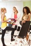 Flickor som talar till den personliga instruktören på idrottshallen Royaltyfri Fotografi
