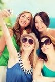 Flickor som tar fotoet i kafé på stranden Arkivbilder