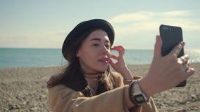 Flickor som tar pics av henne på en strand stock video