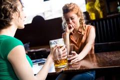 Flickor som tillsammans får på baren Arkivbilder