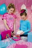Flickor som tjänar som kakan på födelsedagpartiet Arkivbild