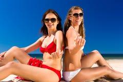 Flickor som tycker om frihet på stranden Arkivbild