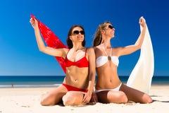 Flickor som tycker om frihet på stranden Fotografering för Bildbyråer