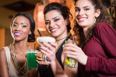 Flickor som tycker om uteliv i en klubba som dricker coctailar Royaltyfria Foton