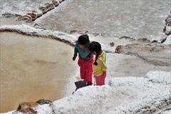 Flickor som undersöker salta lägenheter i Maras, Peru Arkivfoto