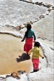 Flickor som undersöker salta lägenheter i Maras, Peru Arkivfoton