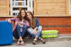 Flickor som väntar på drevsammanträdet på resväskan royaltyfri fotografi