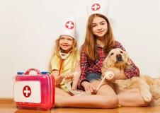 Flickor spelar gulliga doktorer som förbinder deras älsklings- hund Arkivfoto