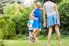 Flickor spelar med rörelse i trädgård fotografering för bildbyråer